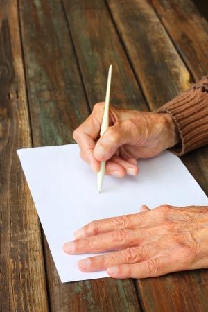 hombre escribiendo: cerca de las manos de los hombres de edad avanzada en la mesa de madera en el papel en blanco Foto de archivo
