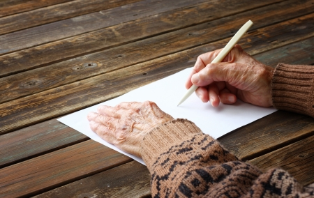 older age: close up of elderly male hands on wooden table   writing on blank paper