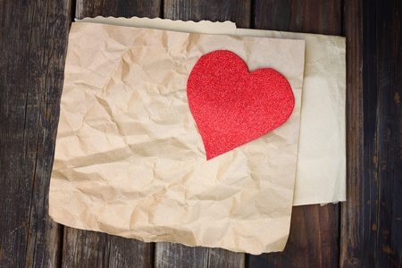 red heart on a crumpled brown paper on wooden background  photo