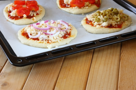 mini oven: mini pizzas in baking dish ready for baking in oven