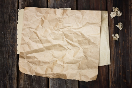brown crumpled paper on wood background photo