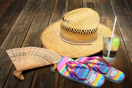 straw hat, flip flops and cold drink on wooden background photo