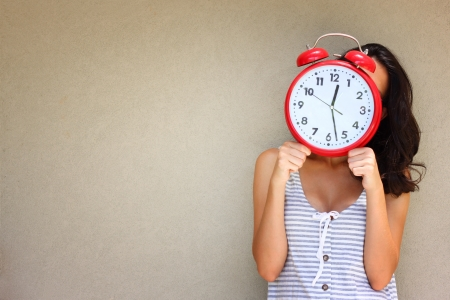 young woman holding clock front of head against a textured wall photo