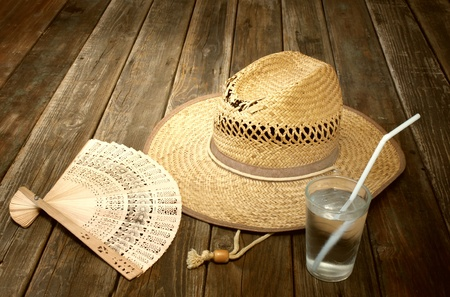 vintage wicker hat, folding fan and cold drink on wooden table photo