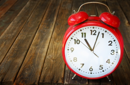 red vintage clock on wooden table photo