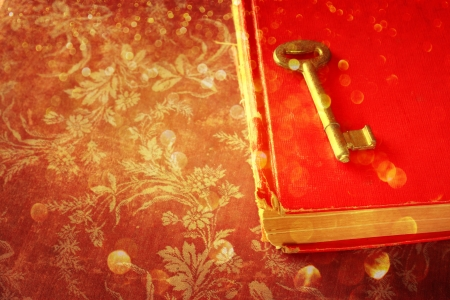 book of revelation: red book and vintage key and golden glitter lights