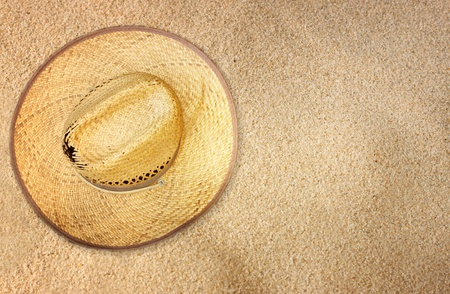 top view of straw hat on beach sand photo