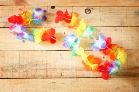 hawaiian lei: Necklace of bright colorful flowers lei on wood background