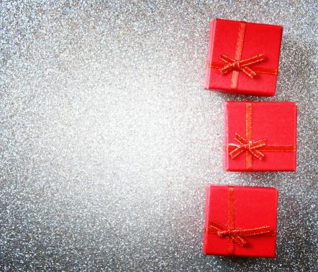 dar un regalo: cajas de regalo de color rojo sobre fondo glittersilver Foto de archivo