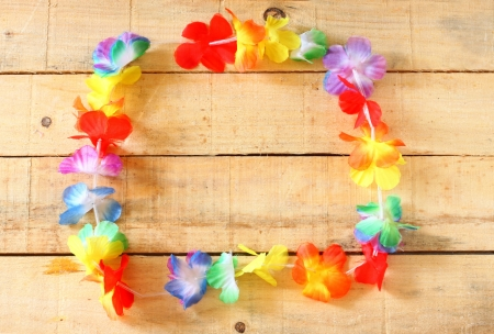 hawaiian lei: Necklace of bright colorful flowers lei on wooden background Stock Photo
