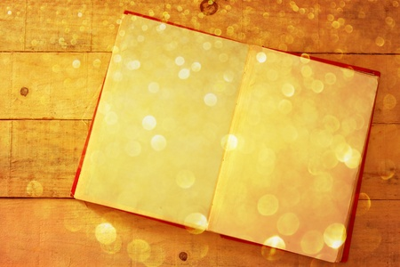 fairytale background: open book on wooden table with glitter gold lights