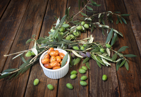 homemade piquant olives, olive tree branch and raw olives  photo