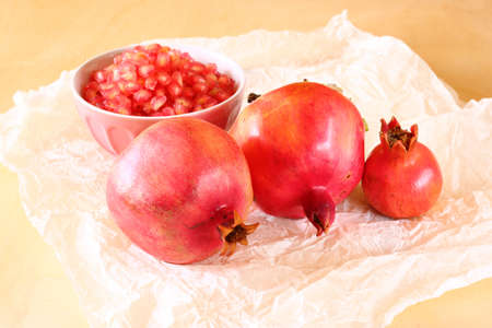 tova: pomegranate on wooden table, and fresh pomegrante seed in bowl