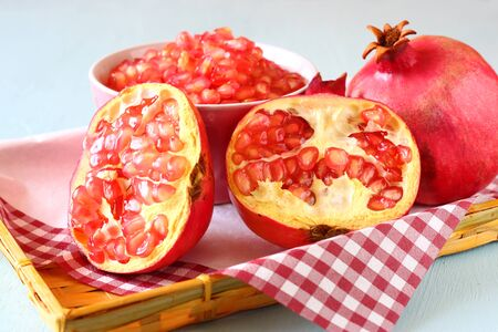 pomegranate on wooden table, and fresh pomegrante seed in bowl photo