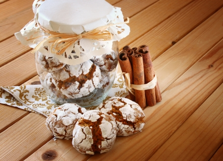 honey cakes  cookie jar and cinnamon sticks on wooden table photo