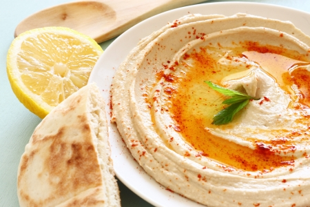 middle eastern food: hummus dip plate and lemon on wooden table