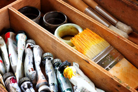 painter wooden case with used oil tubes and brushes photo