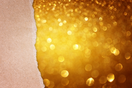 torn paper over golden glitter bokeh lights photo