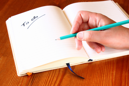 to do list: woman hand holding pencil and opened notebook with a to do list
