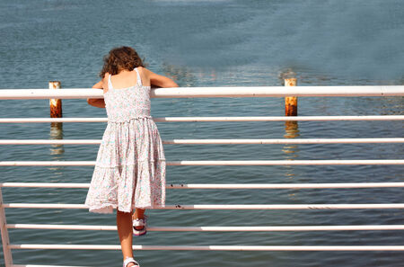 near side: young child standing near fence at sea side Stock Photo
