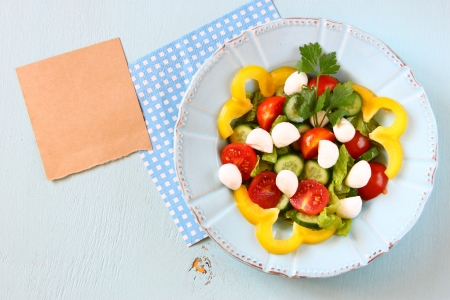 salad with mozzarella and fresh vegetables on wooden table background  top view