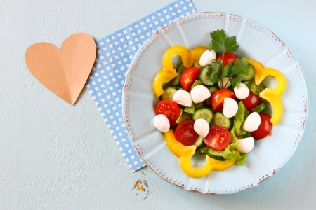 sallad: salad with mozzarella and fresh vegetables on wooden table background  top view