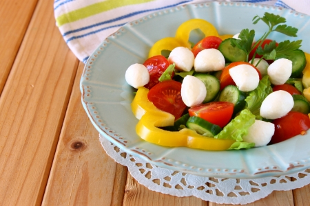 salad with mozzarella and fresh vegetables on wooden table background Stock Photo