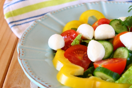 sallad: salad with mozzarella and fresh vegetables on wooden table background Stock Photo