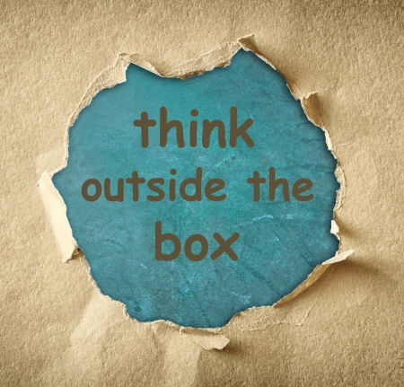 Breakthrough paper hole and the phrase think outside the box written on blue board Stock Photo - 24691054