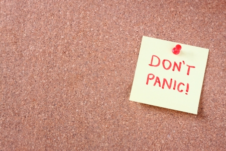 cork board with pinned yellow note and the phrase  dont panic  written on it  room for text  photo