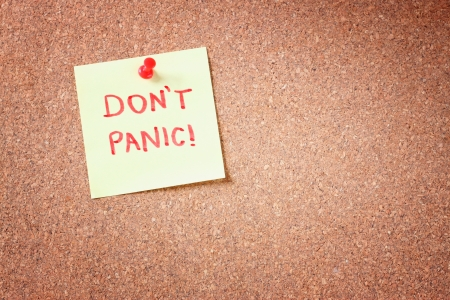 don't care: cork board with pinned yellow note and the phrase  dont panic  written on it  room for text