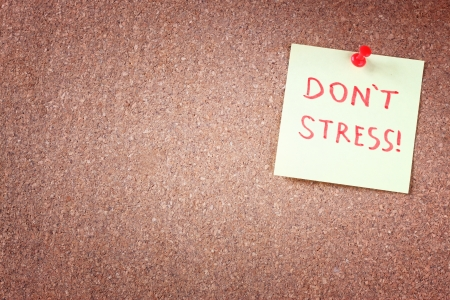 don't care: corkboard with pinned yellow note and the phrase  dont stress  written on it  room for text