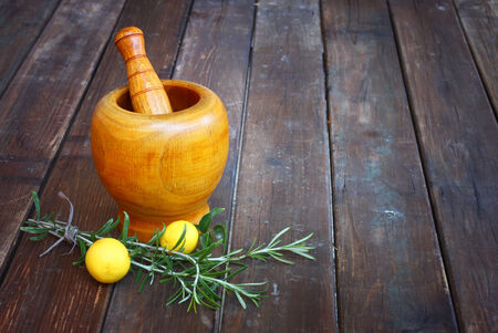 blend: fresh rosemary herbs in wooden pestle and mortar on wooden table