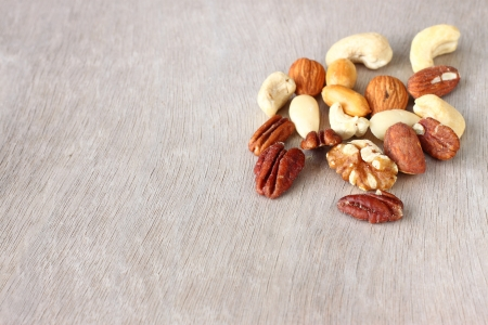 Assorted healthy mixed nuts on wooden textured background   Stock Photo - 24756766