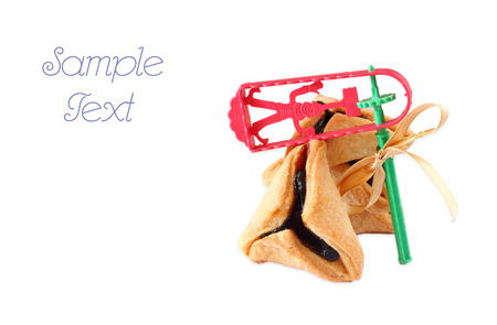 purim: Hamantaschen cookies or hamans ears and Noisemaker for Purim celebration  isolated