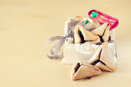 haman: Hamantaschen cookies or hamans ears and Noisemaker for Purim celebration in wooden box  vintage effect