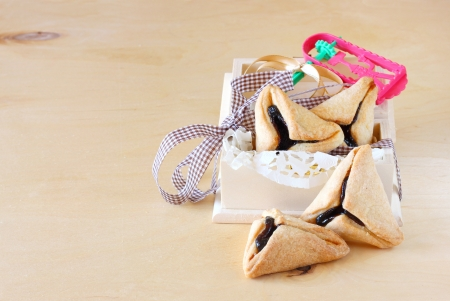 haman: Hamantaschen cookies or hamans ears and Noisemaker for Purim celebration in wooden box
