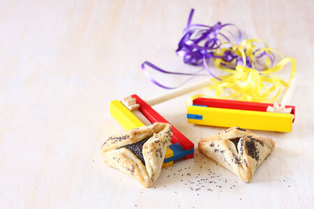 hamantaschen: Hamantaschen cookies or hamans ears for Purim celebration and noisemaker over textured wooden board Stock Photo