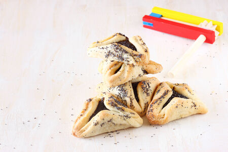 megillah: Hamantaschen cookies or hamans ears for Purim celebration and noisemaker over textured wooden board Stock Photo