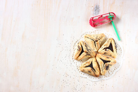 jewish food: Hamantaschen cookies or hamans ears for Purim celebration and noisemaker over textured wooden board Stock Photo