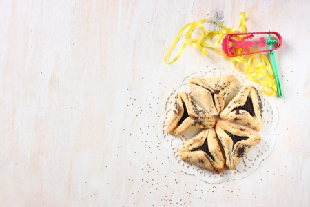 hamantash: Hamantaschen cookies or hamans ears for Purim celebration and noisemaker over textured wooden board Stock Photo