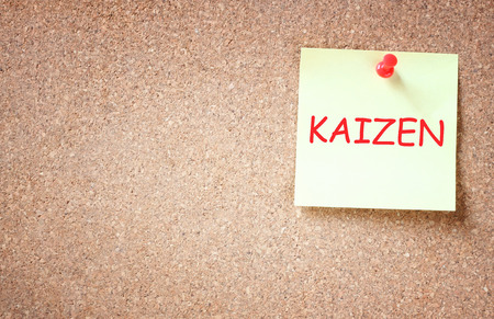 sticky pinned to cork board with the phrase kaizen improvement concept   photo