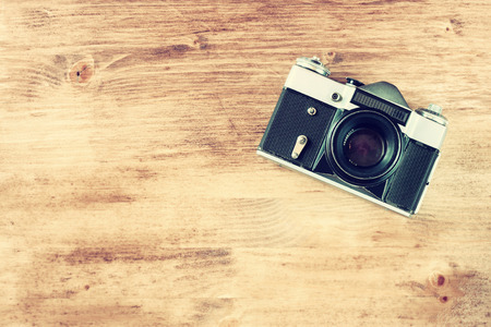 vintage old camera on brown wooden background  room for text  vintage effect process