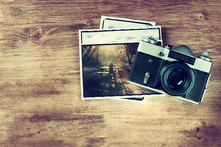 top view of old vintage camera and pictures over wooden brown background  vintage effect process    photo