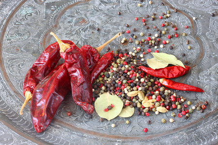 paprica: metal spice grinder with red hot peppers and bay leaf