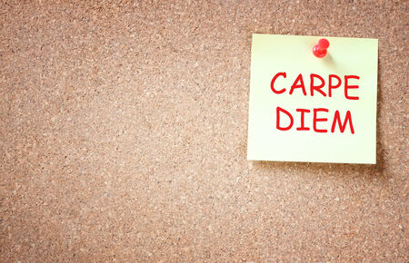 existential: sticky note pinned to corckboard with the phrase carpe diem  room for text