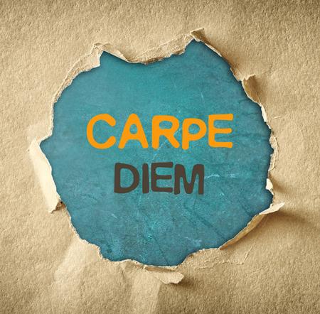 the phrase carpe diem written over chalkboard through hole in torn paper   Stock Photo