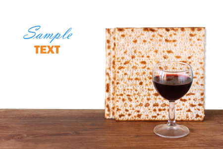 jewish festival: passover background  wine and matzoh  jewish passover bread   over wooden background  isolated over white