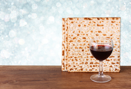 passover background  wine and matzoh  jewish passover bread   over wooden background  glitter background  photo