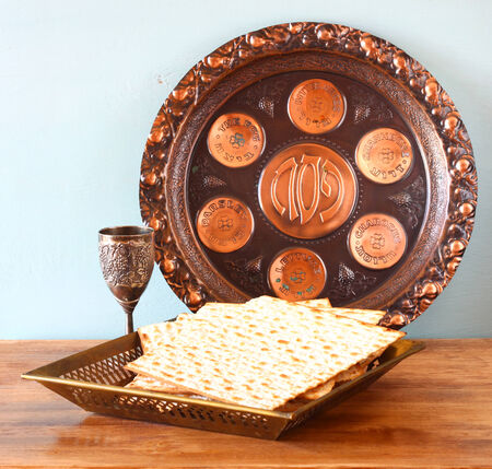 passover background  plate, wine and matzoh  jewish passover bread  over wooden background   photo